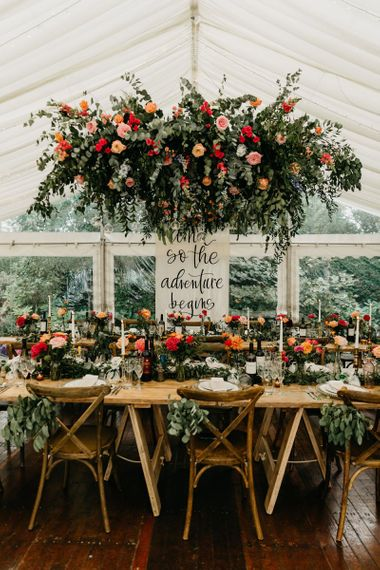 Marquee reception with flag top table sign and hanging flower installation