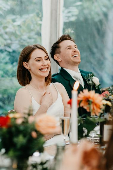 Bride and groom laughing during wedding reception speeches