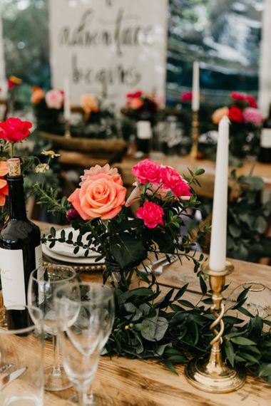 Gold candlesticks and colourful flowers at marquee reception
