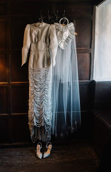 Silver gothic styled wedding dress with long sleeves, cobweb train and corset waist