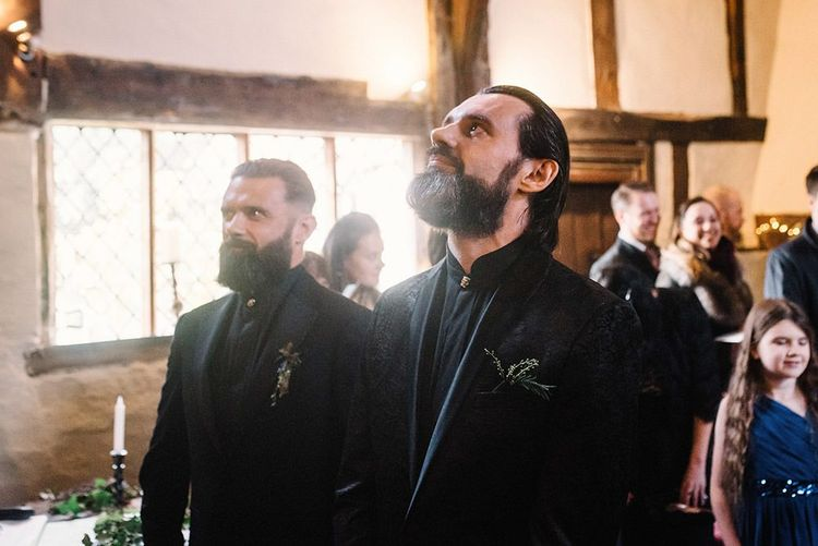 Groom wearing black jacquard suit at Gothic wedding  with cosy styling and foliage
