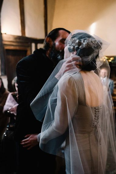 Bride wearing vintage styled floral headpiece with corset waist dress and groom in black suit