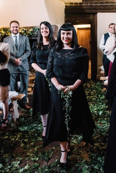 Bridesmaids wearing black laced dresses with foliage decor and bouquets
