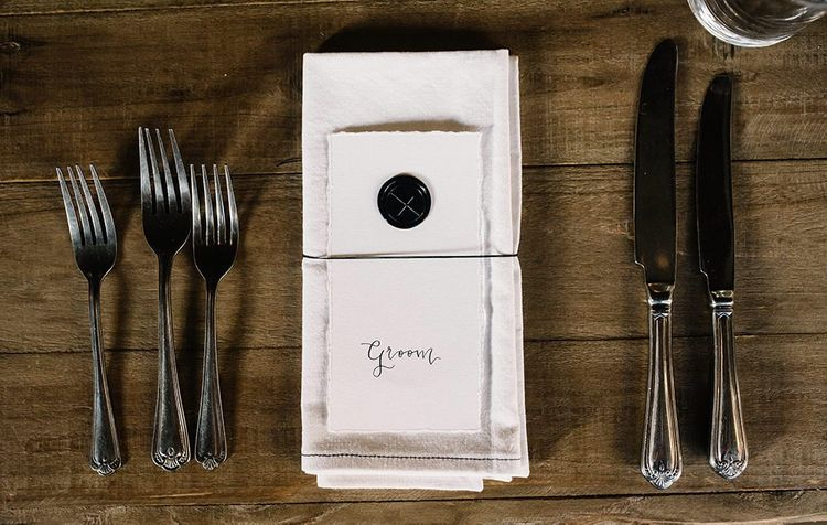 Personalised place settings at gothic wedding with candlelights and foliage decor