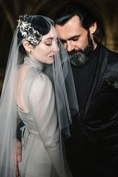 Bride wearing silver gothic styled dress with corset waist, cob-web train and groom in black suit and shirt