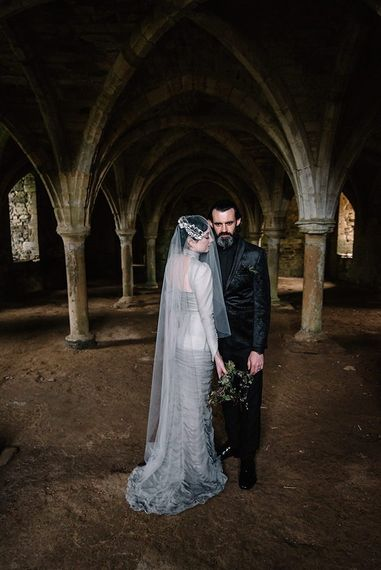 Bride wearing silver gothic styled dress with corset waist, cob-web train and foliage bouquet