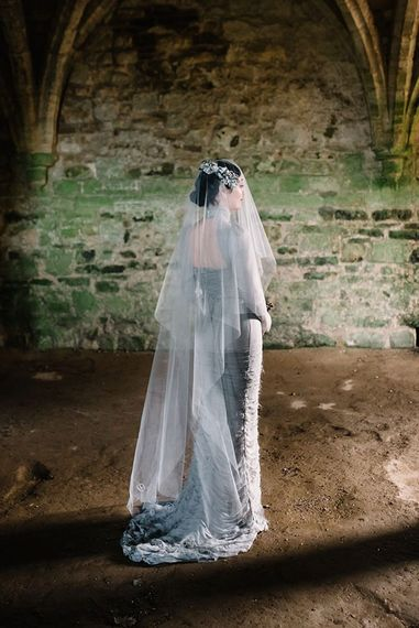 Bride wearing silver gothic styled dress with corset waist, cob-web train and floral headpiece