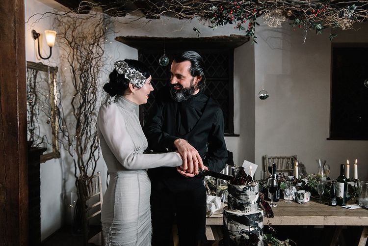 Bride and groom cut the cake at gothic wedding wearing silver dress, vintage floral headpiece and black suit