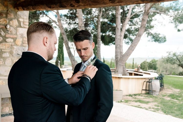 Groom Having His Buttonhole Fitted to Suit