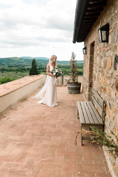 Bride During Preparations With White Flowers In Badgley Mischka Dress