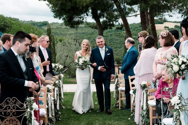 Bride Walks Up The Aisle With Father For Outdoor Ceremony