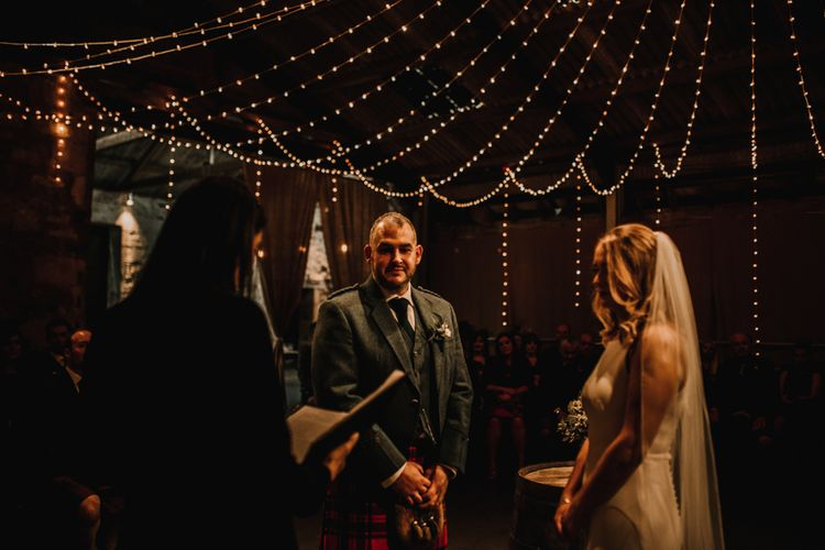 Bride in Anne Priscilla Signature Gown with Halterneck, Keyhole Back and Belt   Floor Length Veil   Groom in Family Mackintosh Tartan Kilt   Kinkell Byre Wedding Venue   Festoon Light Canopy and Indoor Trees for Humanist Wedding in St Andrews   Carla Blain Photography