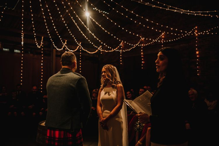Bride in Anne Priscilla Signature Gown with Halterneck, Keyhole Back and Belt   Floor Length Veil   Groom in Mackintosh Tartan Red and Black Kilt with Green Jacket and Waistcoat   Kinkell Byre Wedding Venue   Festoon Light Canopy and Indoor Trees for Humanist Wedding in St Andrews   Carla Blain Photography