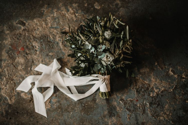 Wedding Bouquet of White Flowers and Green Foliage with White Trailing Ribbon   Festoon Light Canopy and Indoor Trees for Humanist Wedding in St Andrews   Carla Blain Photography