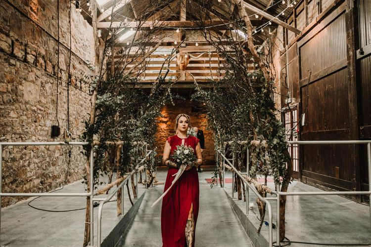 Aisle of Trees   Bridesmaid in Maroon ASOS Dress with Lace Cap Sleeves, Halterneck and Leg Split   Wedding Bouquet of White Flowers and Green Foliage with White Trailing Ribbon   Kinkell Byre Wedding Venue   Festoon Light Canopy and Indoor Trees for Humanist Wedding in St Andrews   Carla Blain Photography