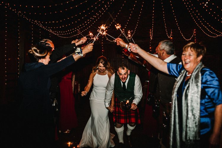 Bride in Anne Priscilla Signature Gown with Halterneck, Keyhole Back and Belt   Groom in Mackintosh Tartan Red and Black Kilt with Green Jacket and Waistcoat   Sparkler Send Off   Festoon Light Canopy and Indoor Trees for Humanist Wedding in St Andrews   Carla Blain Photography