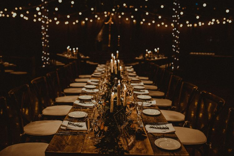 Wooden Banquet Table   Foliage Table Runner   White Tapered Candles   Perspex Table Sign   Rosemary Sprig Place Setting   Kinkell Byre Wedding Venue   Festoon Light Canopy and Indoor Trees for Humanist Wedding in St Andrews   Carla Blain Photography