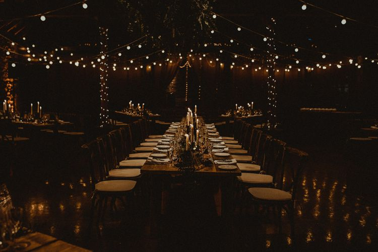 Wooden Banquet Tables   Foliage Table Runners   White Tapered Candles   Rosemary Sprig Place Setting   Kinkell Byre Wedding Venue   Festoon Light Canopy and Indoor Trees for Humanist Wedding in St Andrews   Carla Blain Photography