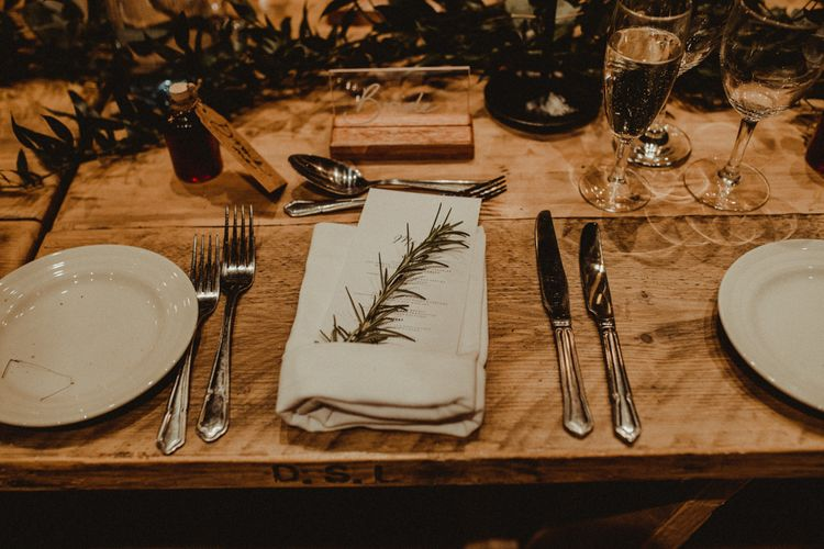 Rosemary Sprig Place Setting   Perspex Name Setting   Alcohol Favour with Drink Me Tag   Wooden Banquet Table   Foliage Table Runner   Kinkell Byre Wedding Venue   Festoon Light Canopy and Indoor Trees for Humanist Wedding in St Andrews   Carla Blain Photography