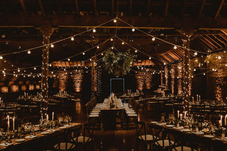 Wooden Banquet Tables   Foliage Table Runners   White Tapered Candles   Rosemary Sprig Place Settings   Foliage Hanging Decoration   Kinkell Byre Wedding Venue   Festoon Light Canopy and Indoor Trees for Humanist Wedding in St Andrews   Carla Blain Photography