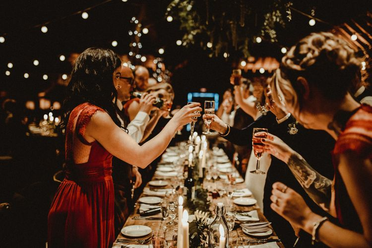 Bridesmaids in Maroon ASOS Dresses with Lace Cap Sleeves, Halterneck and Leg Split   Wooden Banquet Tables   Foliage Table Runners   White Tapered Candles   Kinkell Byre Wedding Venue   Festoon Light Canopy and Indoor Trees for Humanist Wedding in St Andrews   Carla Blain Photography