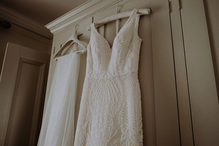 Full Lace Wedding Dress with Veil Hanging Up Before Ceremony