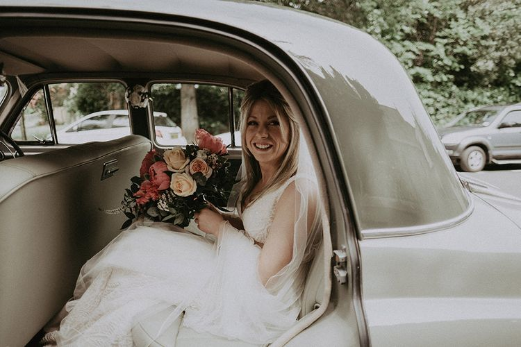 Bride in Vintage Wedding Car with Peony Wedding Bouquet in Lace Dress