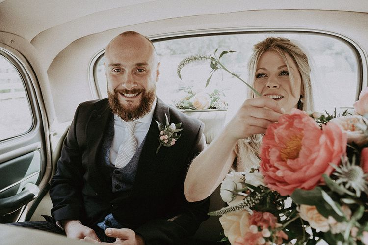 Bride and Groom in Wedding Car with Coral Peony Bouquet
