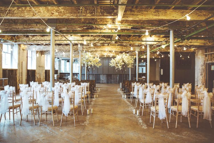 Ceremony Décor at Holmes Mill | Cherry Blossom Tree Altar | White Material Chair Sashes | Pillar Candles | Aisle Petals | Festoon Lights | Lace Bridal Cape Veil & Fishtail Wedding Dress by Pronovias | On Love and Photography