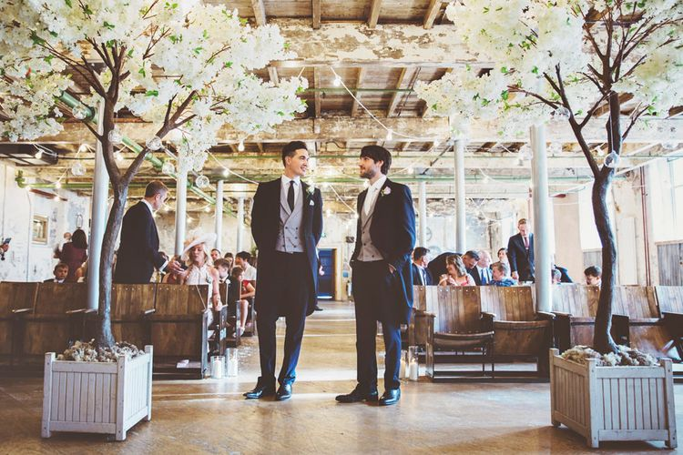 Groom and Best Man Waiting at Altar | Groom in Navy Tails and Grey Waistcoat | Cherry Blossom Tree Altar | Festoon Lights | Lace Bridal Cape Veil & Fishtail Wedding Dress by Pronovias | On Love and Photography