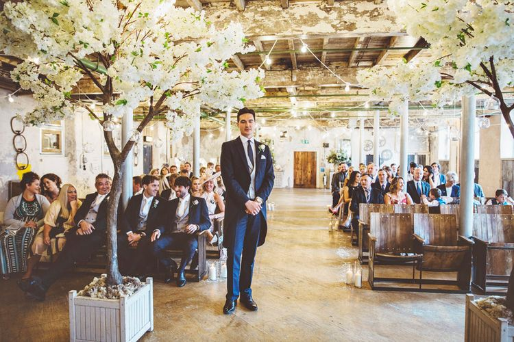 Groom Waiting at Altar | Groom in Navy Tails and Grey Waistcoat | Cherry Blossom Tree Altar | Festoon Lights | Lace Bridal Cape Veil & Fishtail Wedding Dress by Pronovias | On Love and Photography