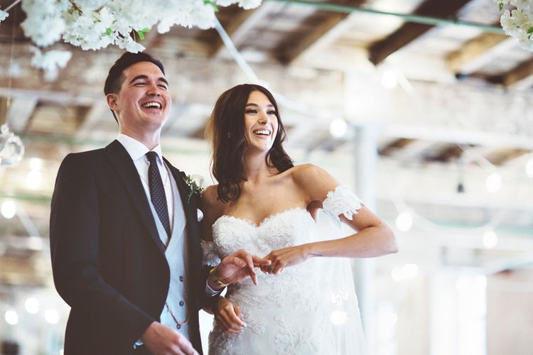 Wedding Ceremony | Bride in Fishtail Pronovias Wedding Dress with Off Shoulder Sleeves and Veil Cape | Groom in Navy Tails and Grey Waistcoat | Bride Wearing Hair Down | Cherry Blossom Tree Altar | Lace Bridal Cape Veil & Fishtail Wedding Dress by Pronovias | On Love and Photography