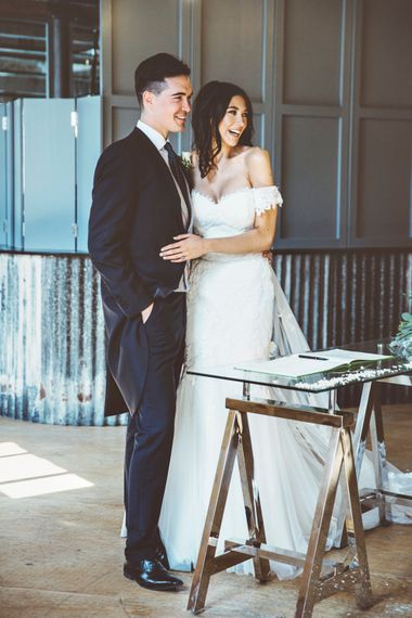 Signing of Register | Bride in Fishtail Pronovias Wedding Dress with Off Shoulder Sleeves and Veil Cape | Groom in Navy Tails and Grey Waistcoat | Bride Wearing Hair Down | Lace Bridal Cape Veil & Fishtail Wedding Dress by Pronovias | On Love and Photography