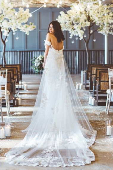 Bride in Embroidered Pronovias Wedding Dress with Off Shoulder Sleeves and Veil Cape | Bride Wearing Hair Down | Bridal Bouquet of White Roses and Greenery | Cherry Blossom Tree Altar | Festoon Lights | Pillar Candles | Aisle Petals | Lace Bridal Cape Veil & Fishtail Wedding Dress by Pronovias | On Love and Photography