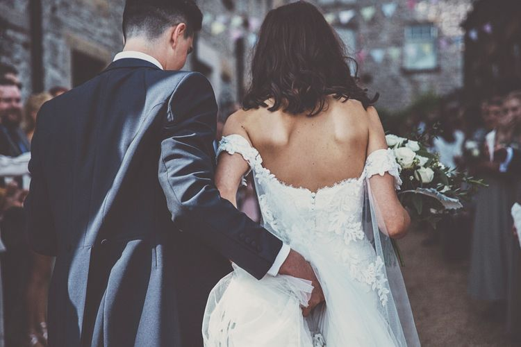 Bride in Fishtail Pronovias Wedding Dress with Off Shoulder Sleeves and Veil Cape | Groom in Navy Tails and Grey Waistcoat | Bride Wearing Hair Down | Bridal Bouquet of White Roses and Greenery | Wedding Bunting | Lace Bridal Cape Veil & Fishtail Wedding Dress by Pronovias | On Love and Photography