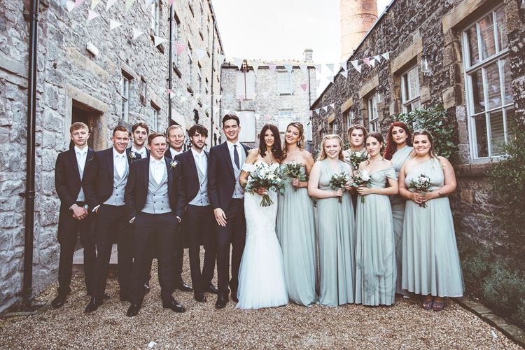 Bride in Fishtail Pronovias Wedding Dress with Off Shoulder Sleeves and Veil Cape | Bride Wearing Hair Down | Bridal Bouquet of White Roses and Greenery | Bridesmaids in Fossil Green Multiway Dresses | Bridesmaid Bouquets of Dusky Purple Roses and Greenery | Groom and Groomsmen in Navy Tails and Grey Waistcoats | Wedding Bunting | Lace Bridal Cape Veil & Fishtail Wedding Dress by Pronovias | On Love and Photography