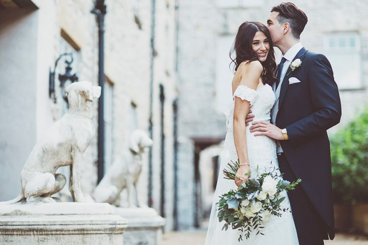 Bride in Fishtail Pronovias Wedding Dress with Off Shoulder Sleeves and Veil Cape | Groom in Navy Tails and Grey Waistcoat | Bride Wearing Hair Down | Bridal Bouquet of White Roses and Greenery | Lace Bridal Cape Veil & Fishtail Wedding Dress by Pronovias | On Love and Photography