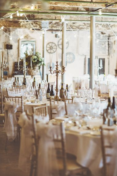 Wedding Reception Décor | Gold Candelabras | White Tapered Candles | White Material Chair Sashes | Festoon Lights | Oversized Floral Urn | Lace Bridal Cape Veil & Fishtail Wedding Dress by Pronovias | On Love and Photography