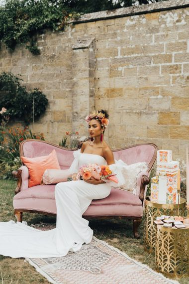 Bride in strapless wedding dress sitting on pink velvet couch