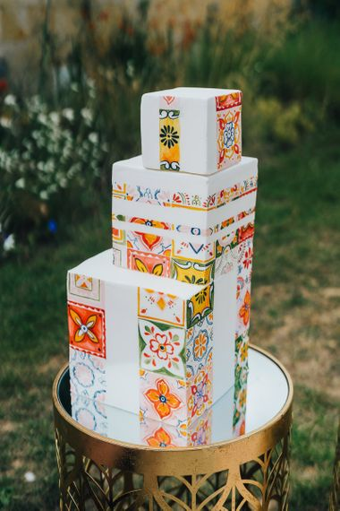 Square wedding cake with colourful tile motif at Chiddingstone Castle