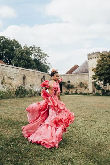 black bride in pink wedding dress at Chiddingstone Castle