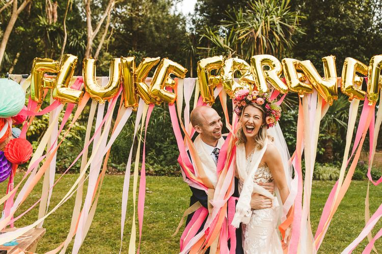 DIY Photo Backdrops using Streamers and Gold Foil Balloons | Colourful Wedding Fiesta at Abbotsbury Wedding in Weymouth, Dorset | Photography by Paul Underhill.