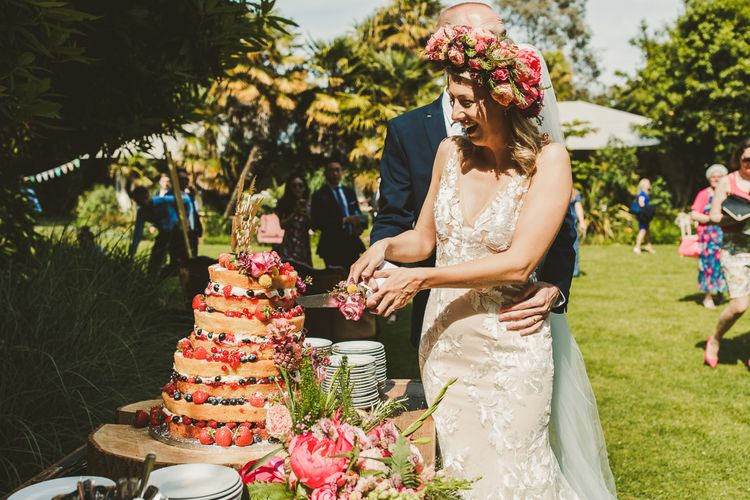 Cutting the Naked Cake with Fruit | Colourful Wedding Fiesta at Abbotsbury Wedding in Weymouth, Dorset | Photography by Paul Underhill.