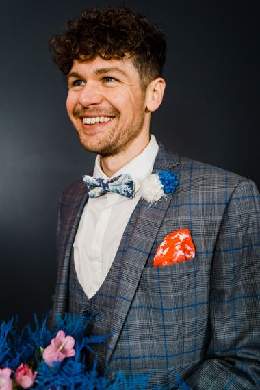 Blue and grey check suit with bow tie for Blue and red wedding bouquet for colourful wedding theme