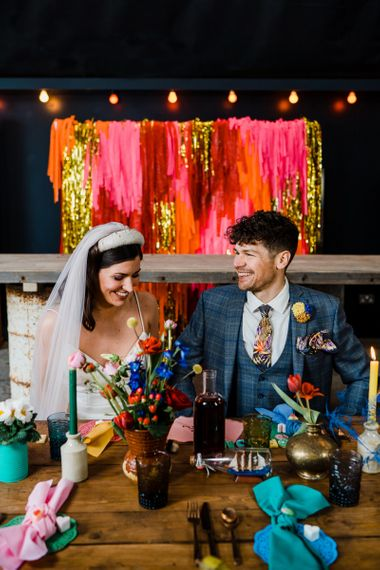 Bride and groom sitting at the reception table with tassle backdrop