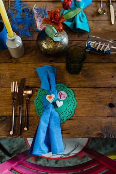Place setting with green doily and blue napkin