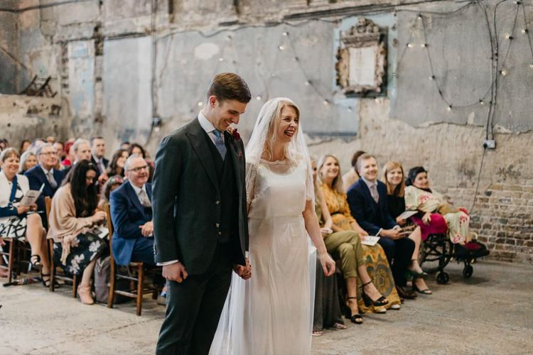 Bride wearing a sophisticated dress with lace tipped veil with her groom at London wedding