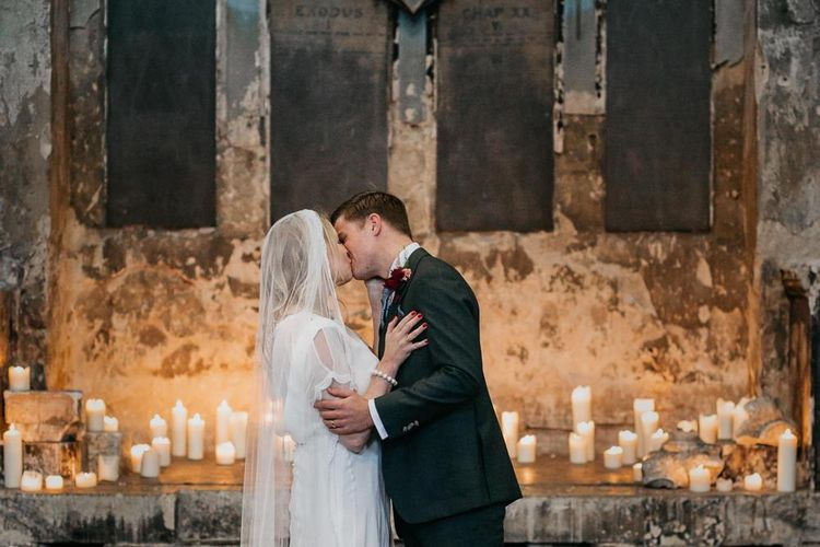 Bride and  grooms first kiss with candle light backdrop