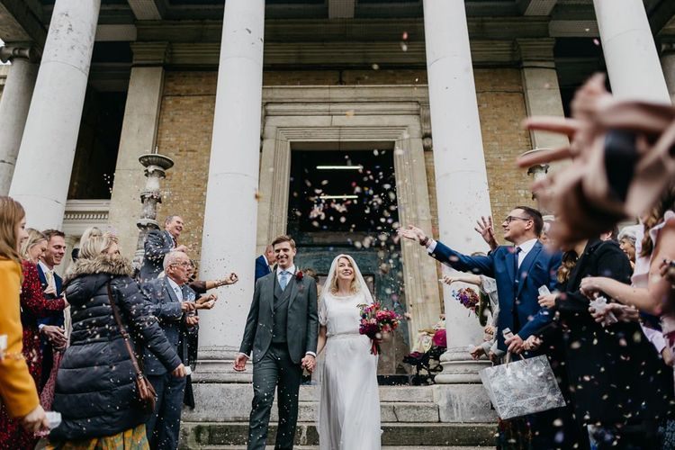Bride and groom confetti shot as they tie the knot at city celebration in London with pine cone wedding decor