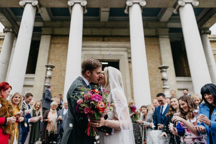 Bride and groom embrace with bright and colour bouquet for a fun and eclectic day